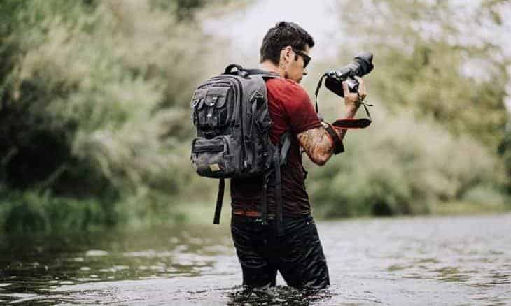 man taking photo while standing in river